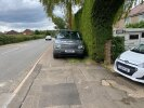 Large Range Rover Parked over footpath and verge causing obstruction to wheelchairs etc. High risk as very busy road.