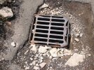 Concrete fixing around drain broken off - now raised metal edging exposed and a danger to all road users