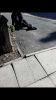 Multiple slabs, cracked, sloped, uneven - kerb edging protrudes by circa 2 inches