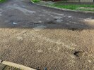 Multiple potholes where road splits on Thorn Close